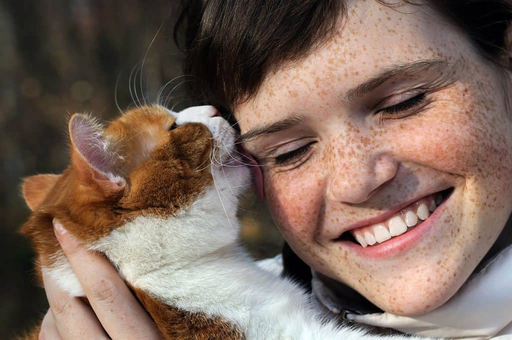 Cat licking a girls face